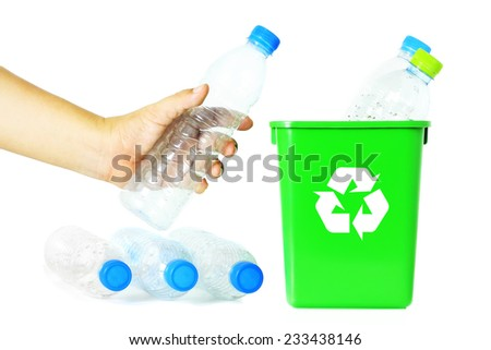 Man's hand putting a plastic bottle into a recycling bin, White background. - stock photo