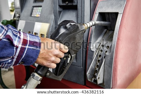 Man's hand removing gas nozzle from gas pump in preparation to refuel - stock photo