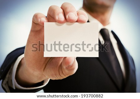 Man's hand showing business card. Black suit and tie. - stock photo