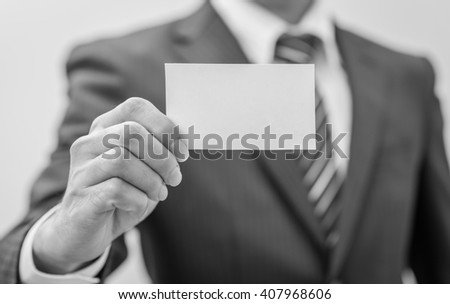 Man's hand showing business card - closeup sho , black and white. - stock photo
