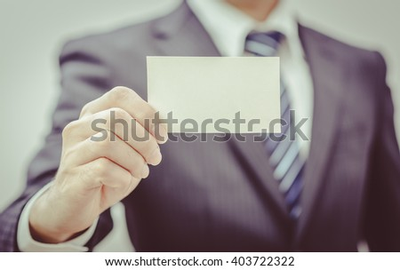 Man's hand showing business card - closeup sho , vintage tone - stock photo