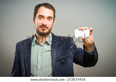 Man's hand showing business card - closeup shot on grey background - stock photo