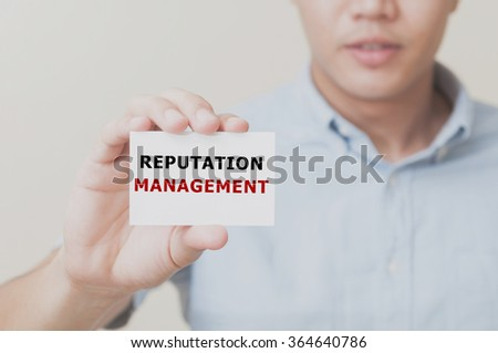 Man's hand showing REPUTATION MANAGEMENT text on the card business card - closeup shot on white background. - stock photo