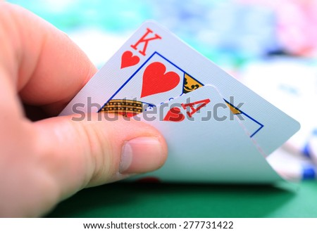 Man's hand showing two ace card token in background - stock photo