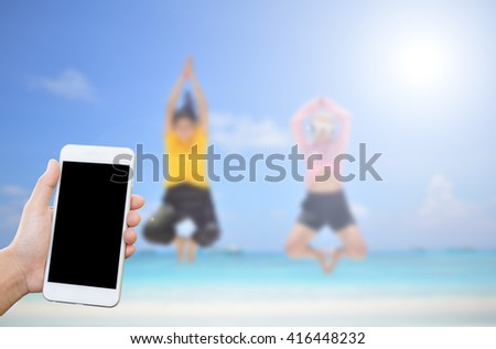 Man's hand shows mobile smartphone,blurred girls jumping on the beach - stock photo
