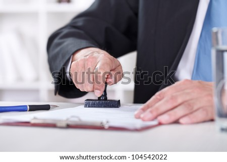 Man�s hand stamping documents, close-up - stock photo