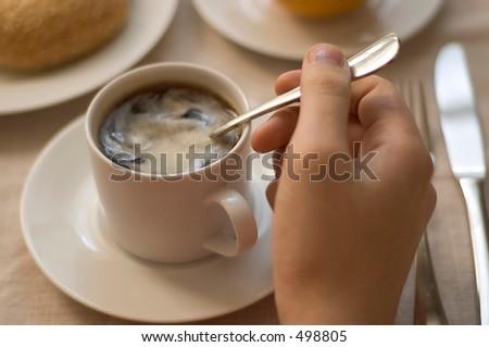 man's hand stirring coffee - stock photo