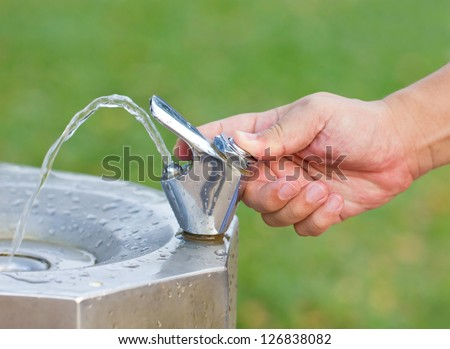 Man's hand turns on the drinking water faucet at public park. - stock photo