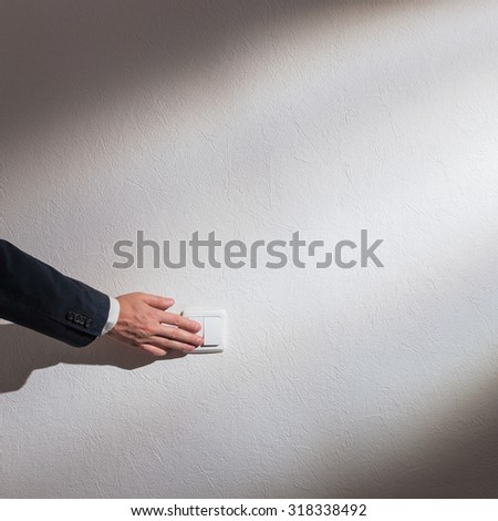 Man's hand turns on the light - stock photo