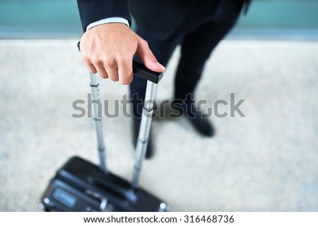 Man's hand with a suitcase - stock photo