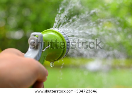 Man's hand with garden hose watering plants