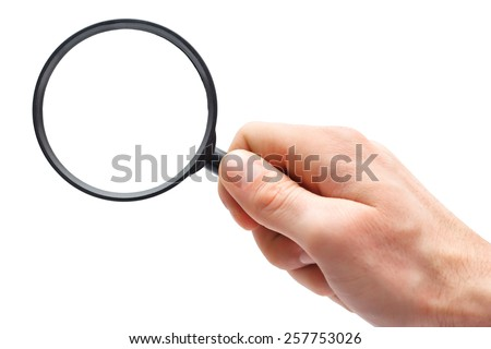 Man's hand with magnifying glass. - stock photo