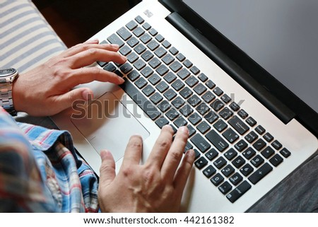 man's hand work with laptop on table, soft focus - stock photo