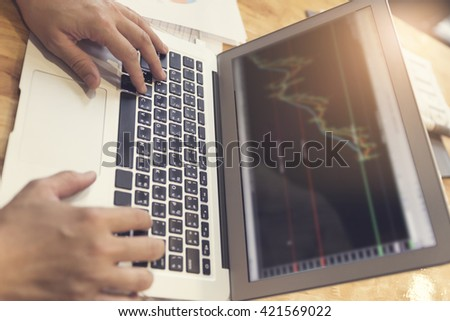 man's hand working with laptop computer with business document on wooden table, selective focus and vintage tone