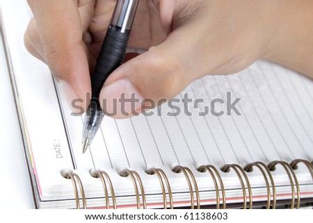 man's hand writing on a book