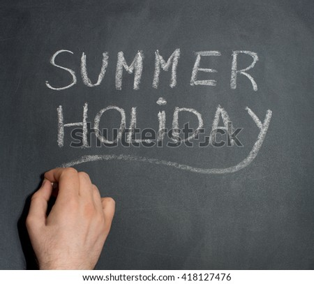 Man's hand writing Summer Holiday text on blackboard.
