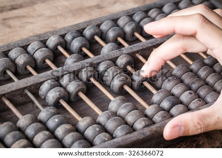 Man's hands accounting with old abacus and hold electronic calculator. picture financial concept - stock photo
