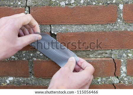 Man's hands applying duct tape over cracks in brick wall. Horizontal shot. - stock photo