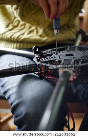 Man's hands assembling multicopter closeup - stock photo