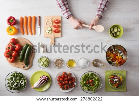 Man's hands cooking at home holding a wooden spoon, fresh vegetables and food ingredients all around, top view - stock photo