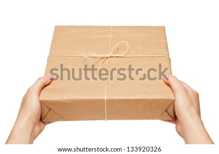 Man's hands gives parcel wrapped in brown paper and tied with rough twine - stock photo