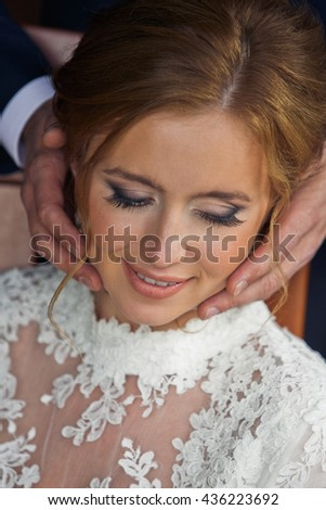 Man's hands hold a stunning bride's face - stock photo