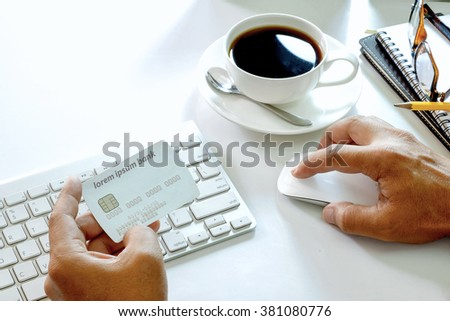 Man's hands holding a credit card and using computer for online shopping. - stock photo