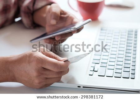 Man's hands holding a credit card and using smart phone for online shopping