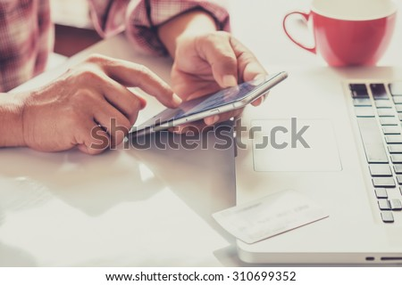 Man's hands holding a credit card and using smart phone for online shopping - stock photo