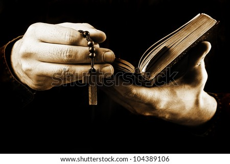 Man's hands holding bible and rosary during prayer - sepia toned on black background - stock photo