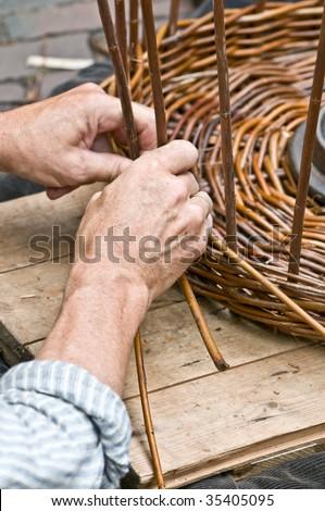 Man's hands making a wicker basket - stock photo