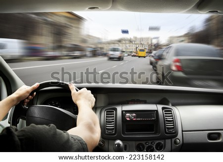 Man's hands of a driver on steering wheel of a minivan car on asphalt road - stock photo