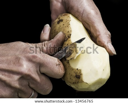 Man's hands peeling potato with serrated knife fading into black background. Shot with macro lens, very detailed image - stock photo