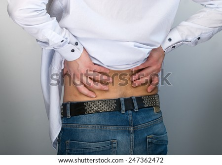 Man's hands pressing against his back suggesting pain. - stock photo