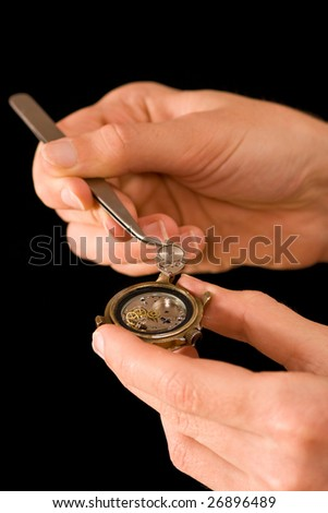 Man's hands repairing old watch, holding a part with tweezers, isolated on black - stock photo