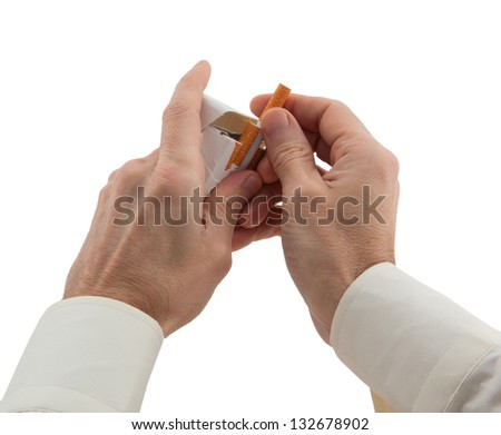 man's hands takes a cigarette out of pack - stock photo