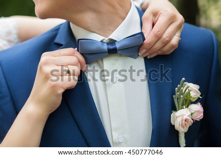 Man's hands touches blue bow-tie in the cage on a white shirt and suit. - stock photo