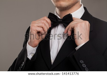 Man's hands touches bow-tie on a suit - stock photo