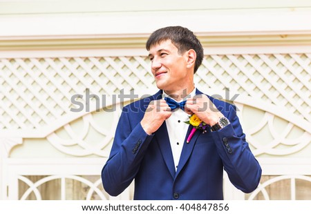 Man's hands touches bow-tie on a suit outdoors - stock photo