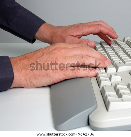 Man's hands typing on a desktop computer keyboard. - stock photo