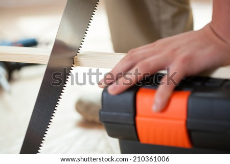 Man's hands using handsaw during renovation, horizontal