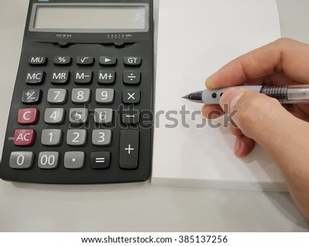 man's hands with a calculator and a pen - stock photo