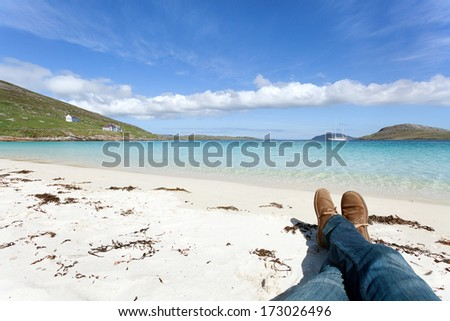 Man's legs relaxing on a scottish white beach . Vatersay, Outer Hebrides of Scotland - stock photo