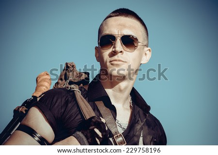 Man's portrait of the soldier against the sky with weapon - stock photo