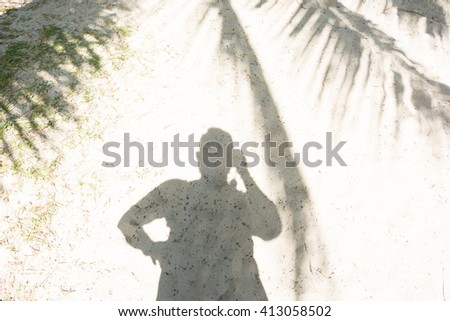 MAN'S SHADOW AND COCONUT PALM TREE LEAVES SHADOW ON SANDY BEACH IN SUNNY DAY TIME - stock photo