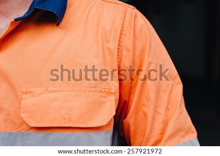 man's shoulder in hi vis workshirt with copyspace for logo - stock photo