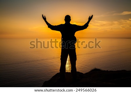 man's silhouette with opened arms standing on the edge of a cliff at sunset