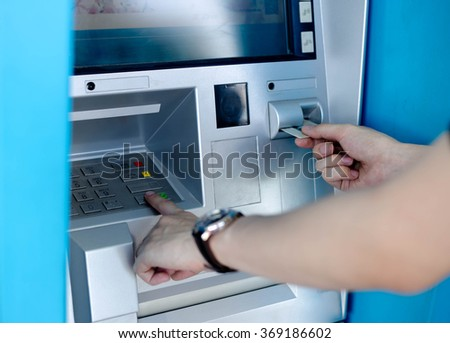 Man's using the ATM machine with cash cards - stock photo