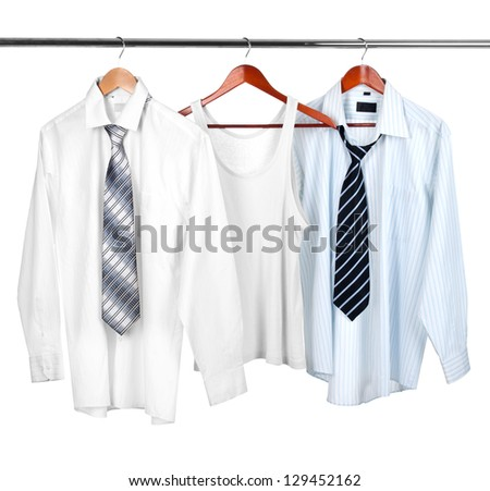 Man's white t-shirt  with white and blue shirts on wooden hanger - stock photo