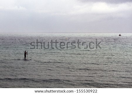 Man sailing on the sea on the surf board